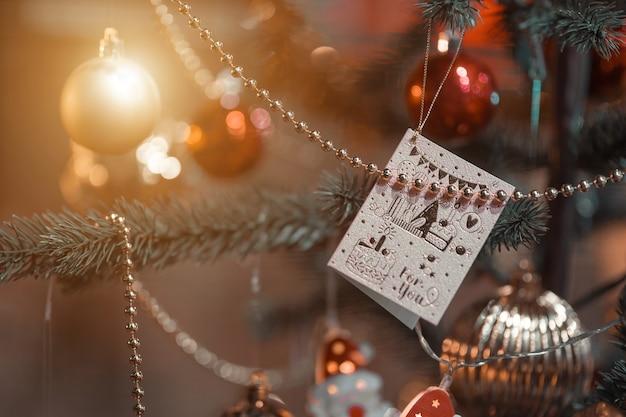 Joyeux x-mas, gros plan de boules colorées, boîte de cadeaux et décoration de colis photo de voeux de noël sur fond d'arbre de noël vert décoration pendant noël et nouvel an.