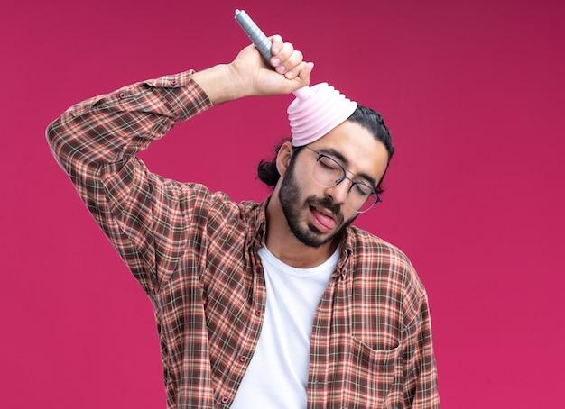 Joyeux avec les yeux fermés jeune beau mec de nettoyage portant un t-shirt mettant le piston sur le front montrant la langue isolée sur le mur rose