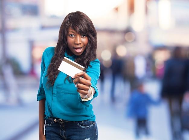 Joyful jeune femme avec une carte de crédit et chemise bleue