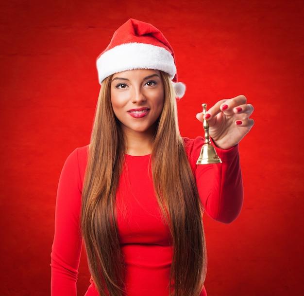 Joyful jeune femme tenant une cloche