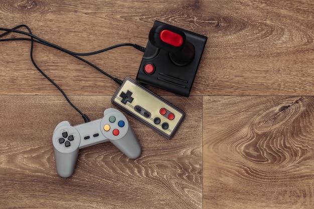Joystick rétro et manette de jeu sur un plancher en bois. vue de dessus