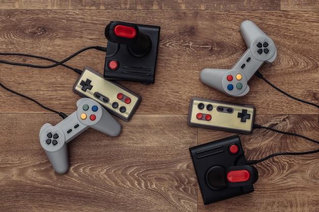 Joysticks rétro et manettes de jeu sur un plancher en bois. vue de dessus