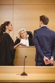 Juge et avocat écoutant le criminel menotté dans la salle d'audience