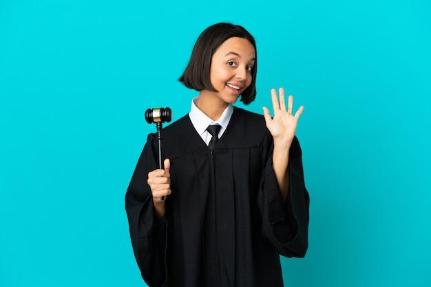 Juge sur fond bleu isolé saluant avec la main avec une expression heureuse