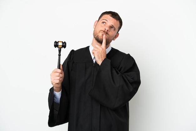Juge homme caucasien isolé sur fond blanc ayant des doutes tout en levant