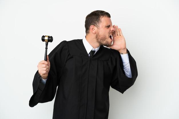 Juge homme caucasien isolé sur fond blanc criant avec la bouche grande ouverte sur le côté