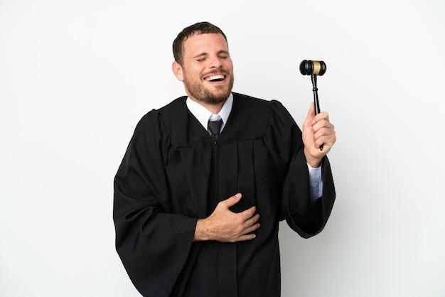 Juge homme caucasien isolé sur fond blanc souriant beaucoup