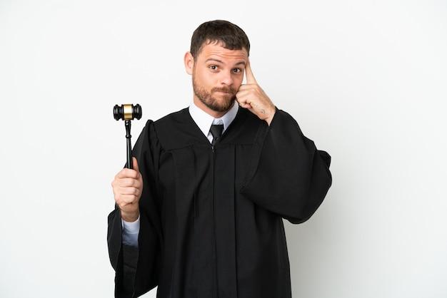 Juge homme de race blanche isolé sur fond blanc en pensant à une idée