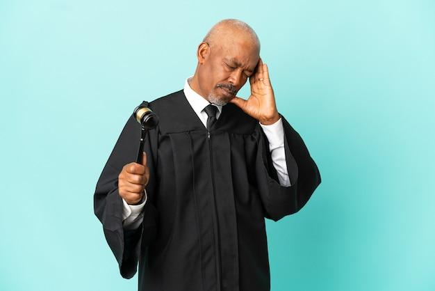 Juge homme senior isolé sur fond bleu avec maux de tête