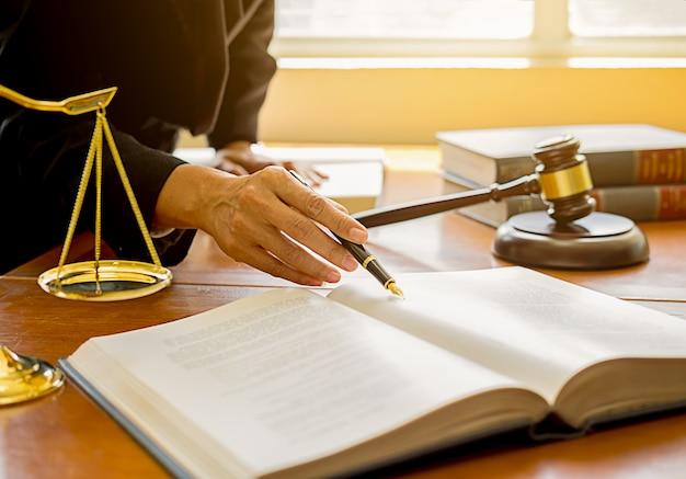 Juge marteau avec les avocats de la justice ayant une réunion d'équipe à l'arrière-plan de la firme d'avocats.