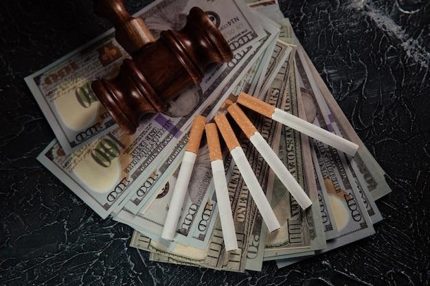 Juge marteau billets et cinq cigarettes sur table grise loi sur le tabac