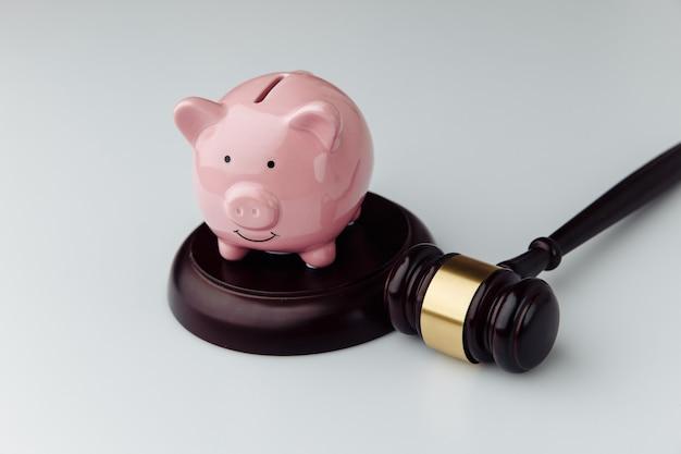 Juge marteau en bois et tirelire rose sur un bureau blanc.