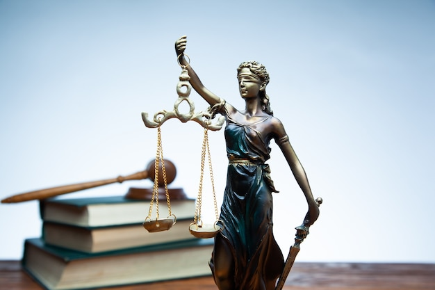 Juge marteau, dame justice et livres sur table rustique blanche