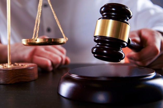 Un juge masculin a battu un marteau en bois sur le bureau. concept d'avocat.
