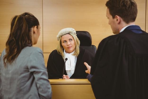 Juge portant robe et perruque écoutant des avocats