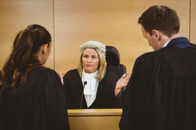 Juge portant une robe et une perruque parlant avec des avocats