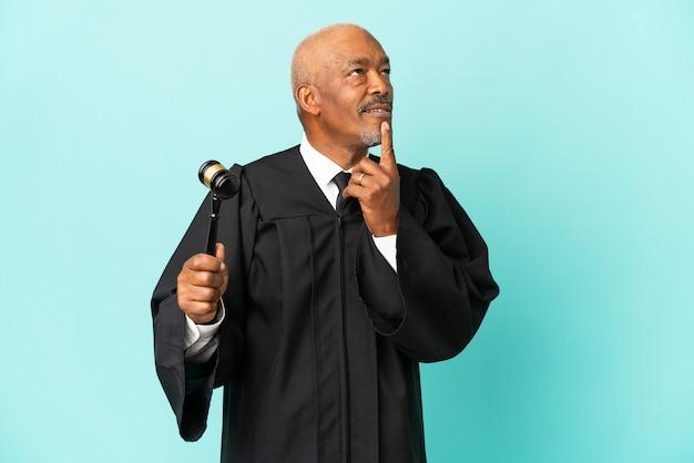 Juge senior homme isolé sur fond bleu ayant des doutes en levant les yeux