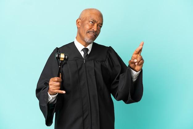 Juge senior homme isolé sur fond bleu avec les doigts croisés et souhaitant le meilleur
