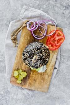 Juicy double burger noir sur une planche à découper en bois.