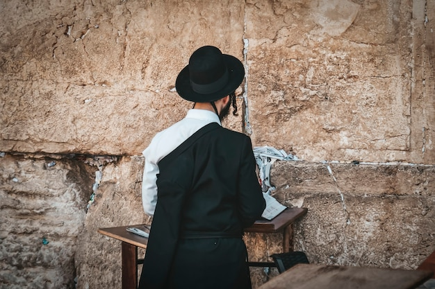Juif orthodoxe religieux priant au mur occidental et lit la torah dans la vieille ville de jérusalem. juifs orthodoxes