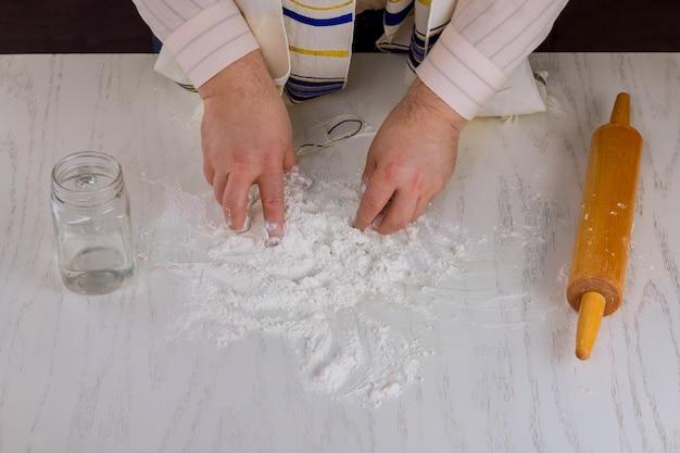 Un juif orthodoxe se prépare pour le jour de la fête juive à la main fait de la matza casher plat