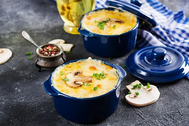 Julienne de champignons au four avec poulet et fromage en pot.