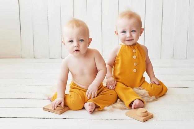 Jumeaux bébé en costume orange posant
