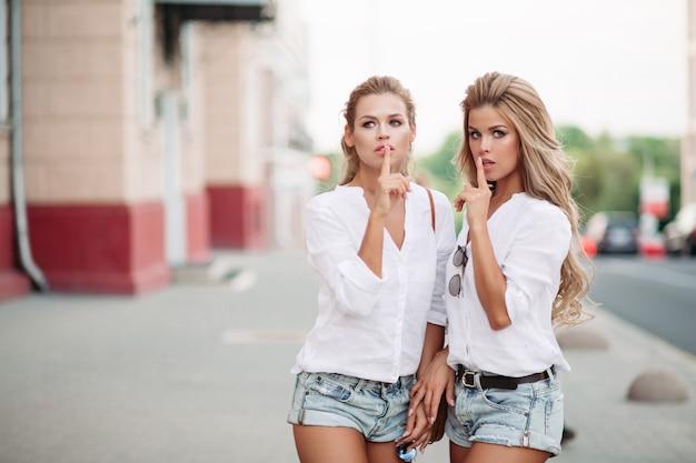 Jumeaux de belles femmes montrant la paix et posant émotionnellement