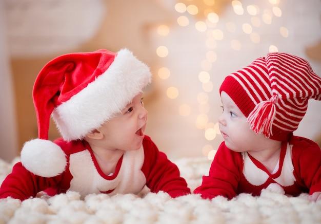 Jumeaux en costumes du nouvel an, allongés sur le lit, souriant et se réjouissant