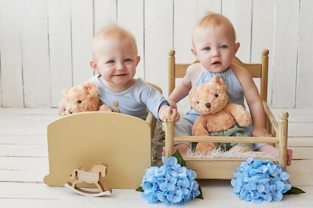 Jumeaux garçons en pyjama bleu avec ours en peluche et bouquets de fleurs
