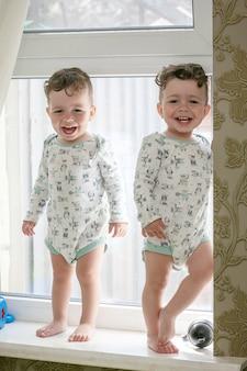 Jumeaux joyeux - les frères se tiennent sur le rebord de la fenêtre