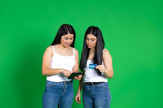 Des jumeaux avec une tablette et une carte bancaire effectuent un paiement en ligne