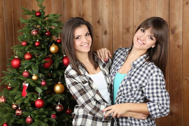Jumelles de belles filles près de l'arbre de noël à la maison