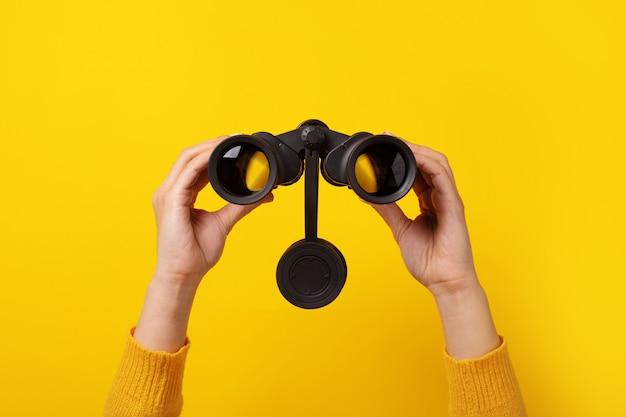 Jumelles à la main sur fond jaune, concept de recherche.