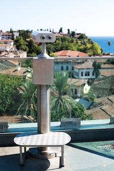 Jumelles sur une plate-forme d'observation avec vue sur la mer et les toits de tuiles rouges