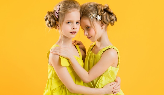 Des jumelles sont assises sur une chaise sur un t-shirt jaune.