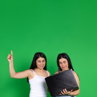 Jumelles sur un tenant un ordinateur portable, pointe le doigt vers le haut