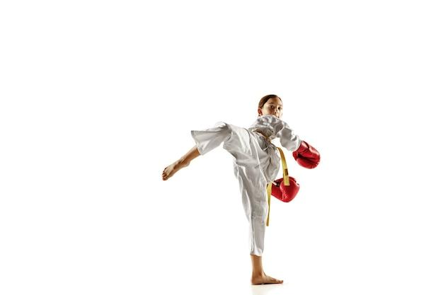 Junior confiant en kimono pratiquant le combat au corps à corps, les arts martiaux. jeune combattante avec entraînement de ceinture jaune sur mur blanc. concept de mode de vie sain, sport, action.