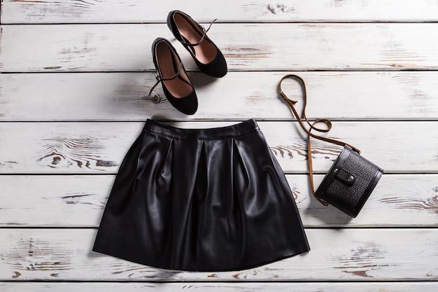Jupe en cuir et chaussures en daim. jupe et chaussures sur étagère. vêtements à la mode pour les filles modernes. les vêtements de soirée à la mode de la dame.