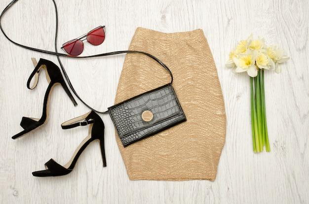 Jupe dorée, chaussures, pochette, lunettes et bouquet de jonquilles.