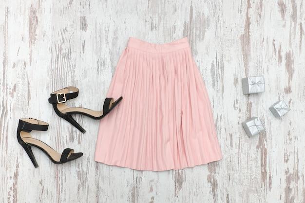 Jupe rose et chaussures noires.