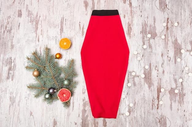 Jupe rouge, branche d'épinette et guirlande sur fond de bois. concept à la mode.