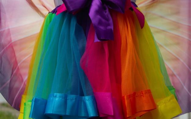 Une jupe en tissu rouge, orange, bleu, bleu, jaune, vert et rose avec des noeuds roses et violets.