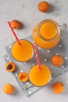 Jus d'abricot à la pulpe dans deux verres et une cruche sur une surface grise, format vertical, vue d'en haut