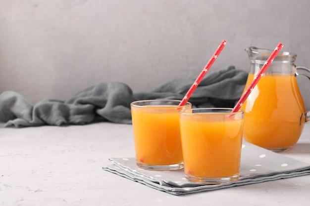 Jus d'abricot à la pulpe dans deux verres et une cruche sur une surface grise avec place pour le texte, format horizontal