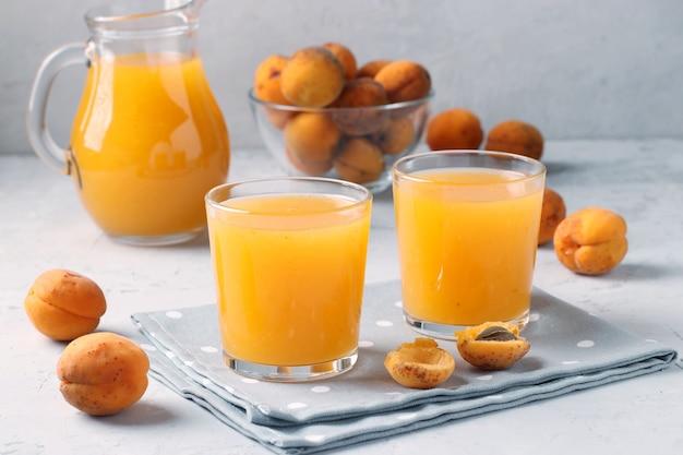 Jus d'abricot à la pulpe dans deux verres et pichet sur fond gris, format horizontal