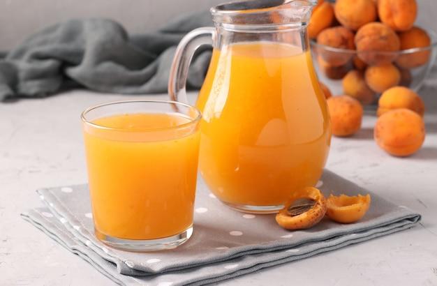 Jus d'abricot avec de la pulpe en verre et verseuse sur fond gris, format horizontal, gros plan