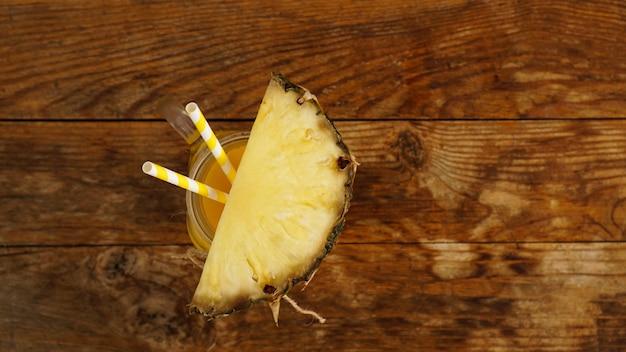Jus d'ananas sur un fond en bois. un bocal en verre avec du jus et une tranche d'ananas frais. fruits exotiques et jus sain avec des vitamines