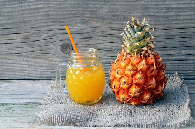 Jus d'ananas fraîchement pressé dans une tasse en verre avec paille et fruits ananas mûrs sur la vieille table en bois. concept d'alimentation saine, de régime ou de nourriture végétalienne.