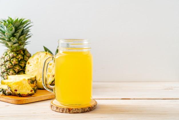 Jus d'ananas frais sur la surface du bois